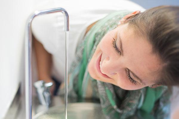 Junge Frau genießt Trinkwasser aus der Leitung.