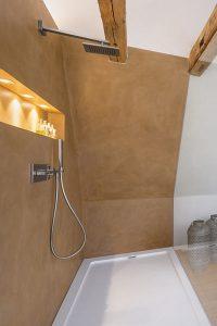 Das Wandelement links nimmt die Installation für die Dusche auf und teilt den Raum in Bad- und Schlafbereich.